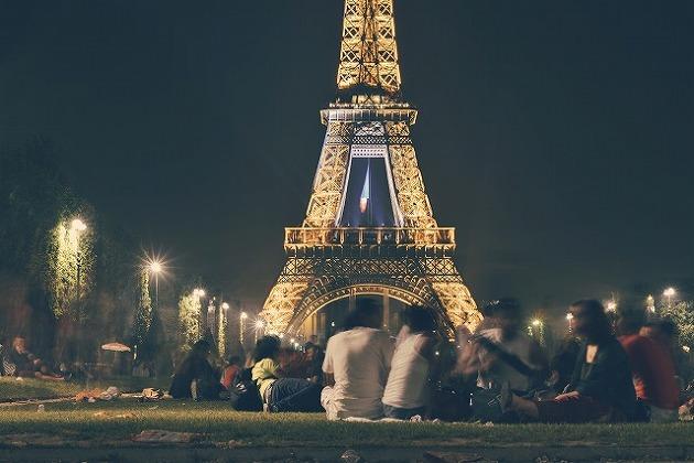 Group Of People Socialising In Front Of Eifel Tower At Night.jpg